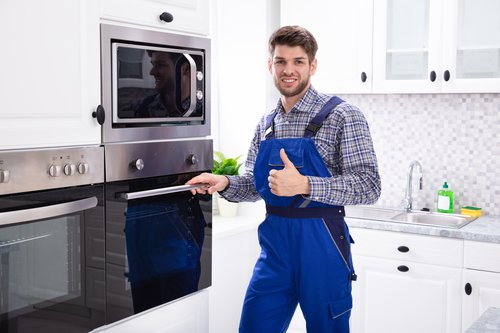 male technician standing in the kitchen in-front of wall oven