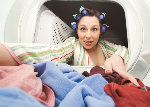 woman reaching in dryer for clothes